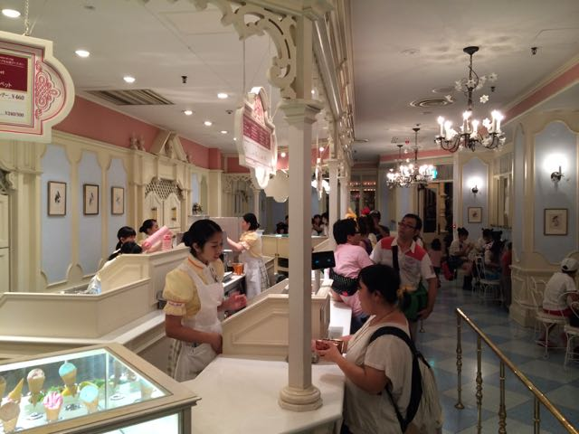 A Disney Cast Member helping a guest at Tokyo Disneyland with their ice cream. Taking an ordinary transaction and making a guest feel special is at the heart of great guest service. Photo by J. Jeff Kober.